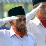 Terpidana kasus terorisme Umar Patek (kiri) memberi hormat ketika menjadi pengibar bendera merah putih pada upacara memperingati Hari Kebangkitan Nasional (Harkitnas) di Lapas Porong, Sidoarjo, Jawa Timur, 20 Mei 2015. ANTARA FOTO