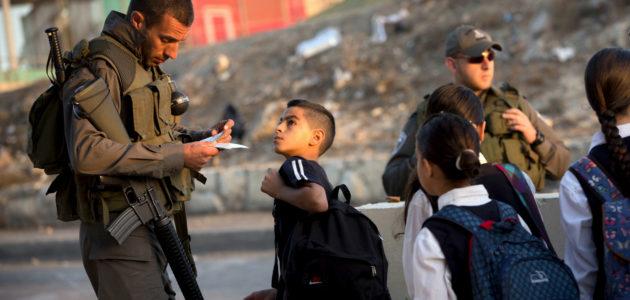 Polisi Israel memeriksa kartu identitas anak-anak sekolah Palestina di sebuah pos pemeriksaan di Yerusalem. (Oded Balilty | AP)