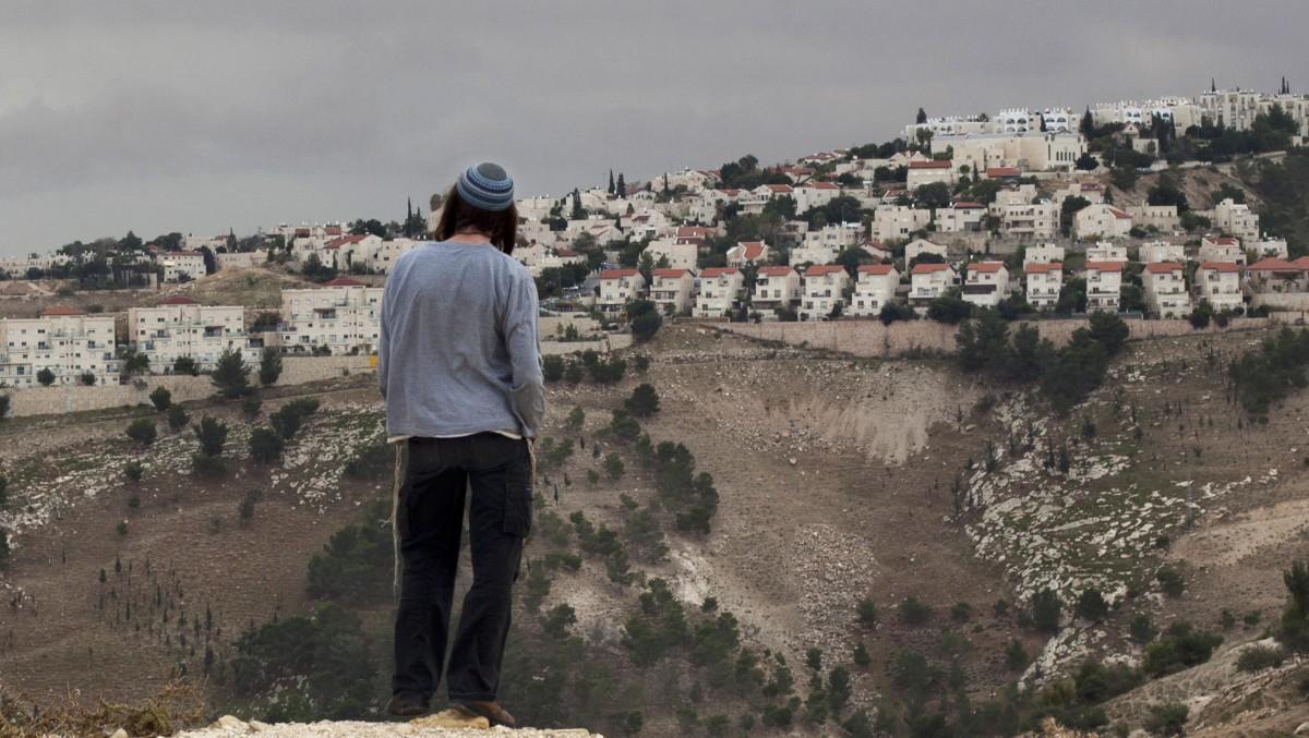 Seorang pemukim Yahudi memandang permukiman Tepi Barat Maaleh Adumim, dari daerah E-1 di pinggiran timur Yerusalem, 5 Desember 2012. (Sebastian Scheiner | AP )