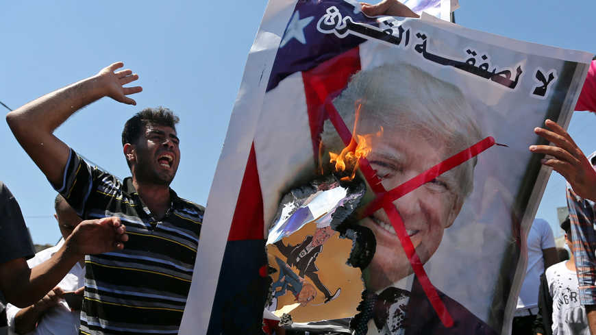 Palestinian demonstrators burn a crossed-out poster depicting U.S. President Trump during a protest against Bahrain's workshop for U.S. Middle East peace plan, in the southern Gaza Strip