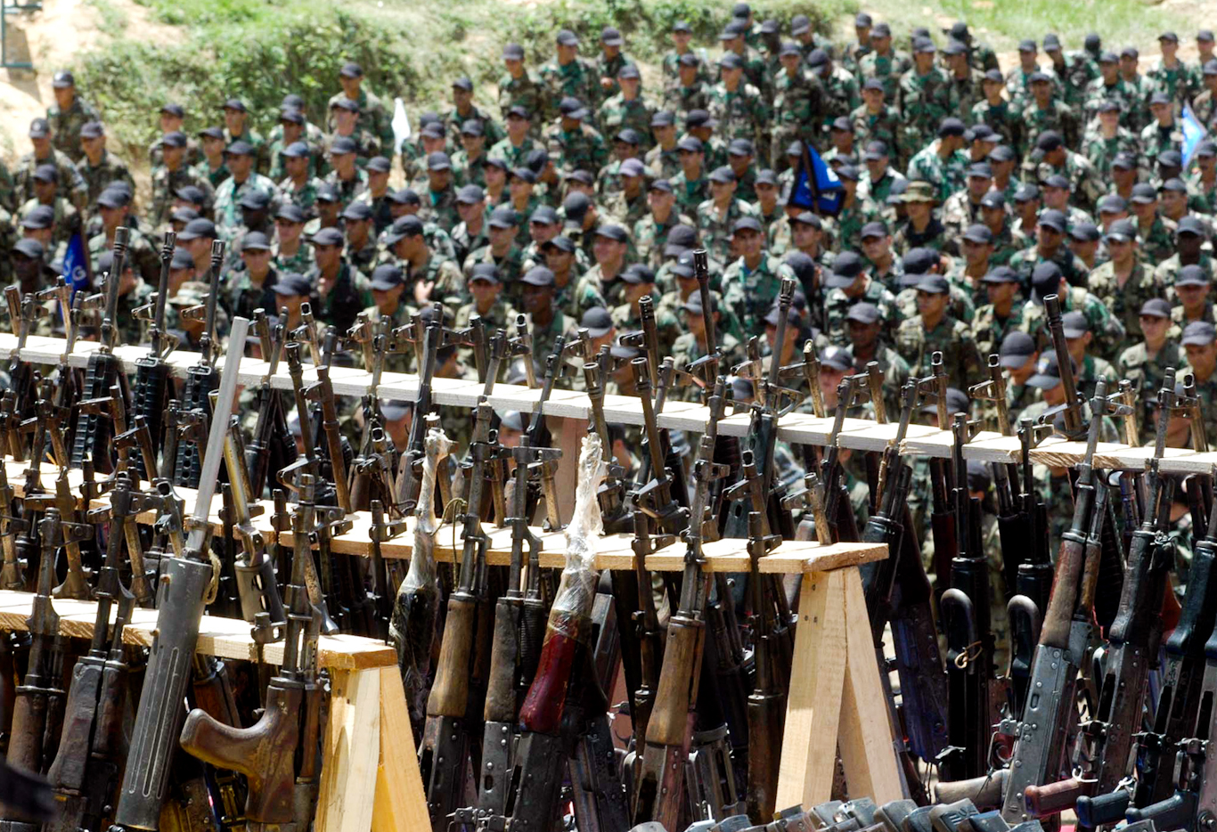 """FILE - In this Aug. 1, 2005 file photo, paramilitary fighters from the """"Heroes of Granada"""" faction of the United Self-Defense Forces of Colombia, or AUC, attend a demobilization ceremony in Cristales, Colombia. Hundreds of right-wing paramilitaries are expected to walk free from prison beginning in March 2014 after serving eight-year sentences for crimes that normally carry more than triple the prison terms. Their lenient sentences were enshrined in a 2005 """"Justice and Peace"""" law that provided a legal framework for the militias' supposed dismantling under a peace deal with the government of then-President Alvaro Uribe. (AP Photo/Luis Benavides, File)"""